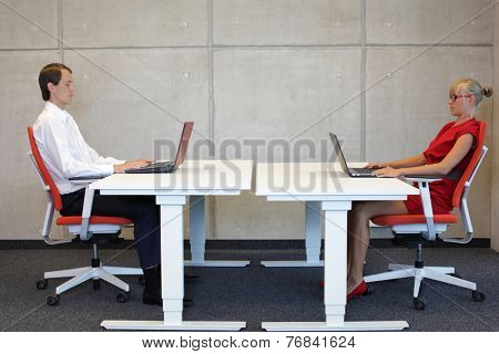 business man and woman in correct sitting posture at workstations in the office