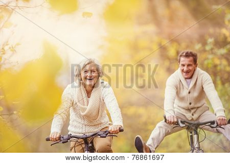 Active seniors ridding bike and having fun