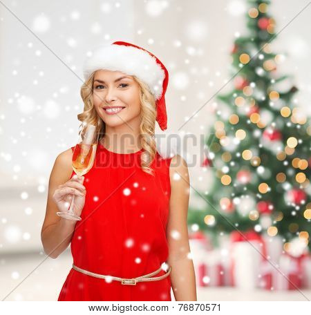 party, drinks celebration and people concept - smiling woman in santa helper hat and red dress with glass of champagne over living room and christmas tree background