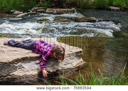 Young Girl Dipping Her Hand In The Water