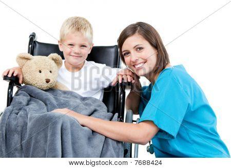 Doctora agradable llevar a Adorable niño pequeño con su osito de peluche en la silla de ruedas