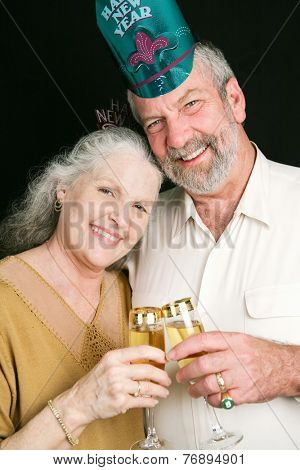Beautiful senior couple toasting in the New Year with champagne.  Black background.