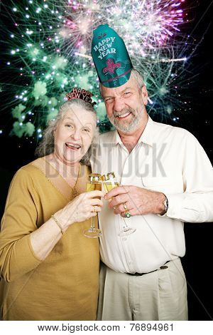 Senior couple a bit drunk at a New Year's Eve party with fireworks going off in the background