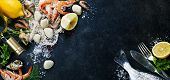 Delicious fresh fish and seafood on dark vintage background. Fish, clams and  shrimps with aromatic herbs, spices and vegetables - healthy food, diet or cooking concept poster