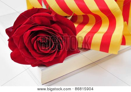 a red rose and the catalan flag on a book for Sant Jordi, the Saint Georges Day, when it is tradition to give red roses and books in Catalonia, Spain poster