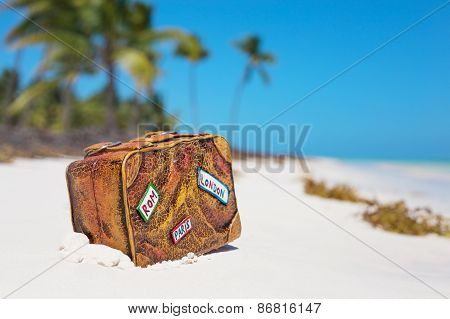 Travel suitcase toy on the beach
