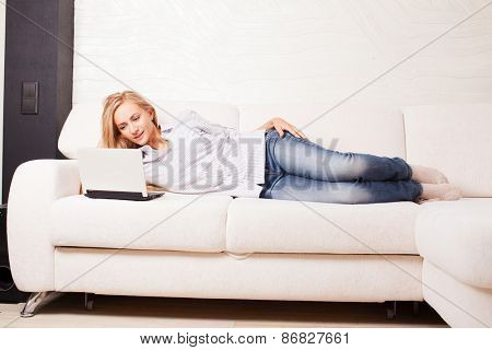 Woman on the sofa with laptop. Happy female with computer at hame
