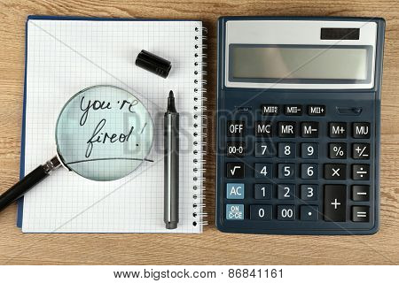 Message You're Fired on notebook with calculator, marker and magnifying glass on wooden table, closeup