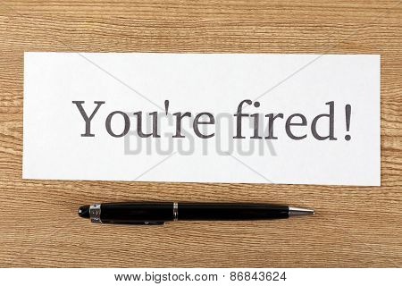 Message You're Fired on sheet of paper with pen on wooden table, top view