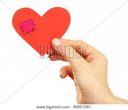 Female hand holding broken heart with patch isolated on white