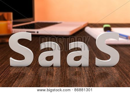 SaaS - Software as a Service - letters on wooden desk with laptop computer and a notebook. 3d render illustration. poster