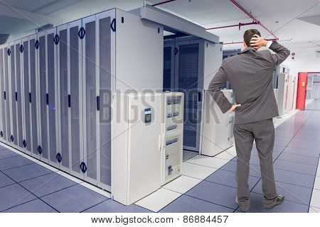Young businessman standing back to camera scratching his head against data center
