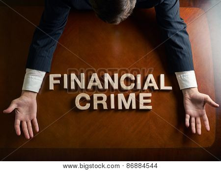 Phrase Financial Crime made of wooden block letters and devastated middle aged caucasian man in a black suit sitting at the table, top view composition with dramatic lighting poster