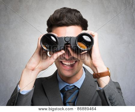 Businessman watching through binoculars in search of new opportunities