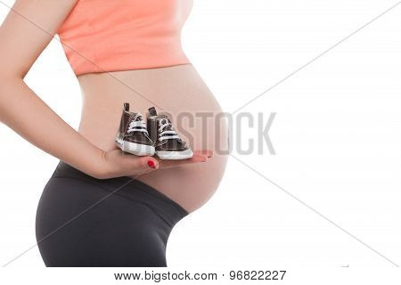 Pregnant woman holding pair of small male shoes for baby
