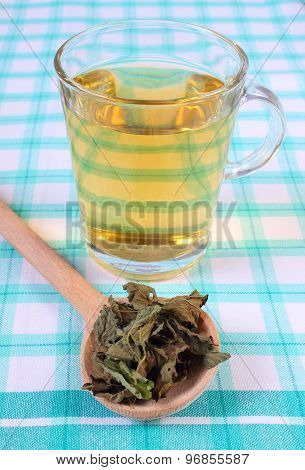 Dried Lemon Balm With Spoon And Glass Of Herbal Drink On Tablecloth