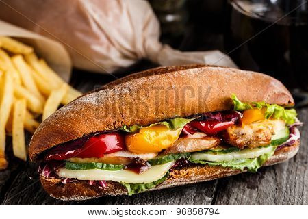 Chicken sandwich, fries and glass of soda