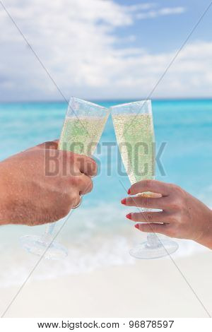 Clink Glasses With Champagne At Sandy Beach