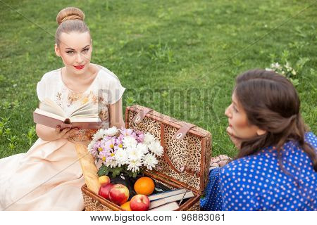 Cheerful young girls are making picnic in park