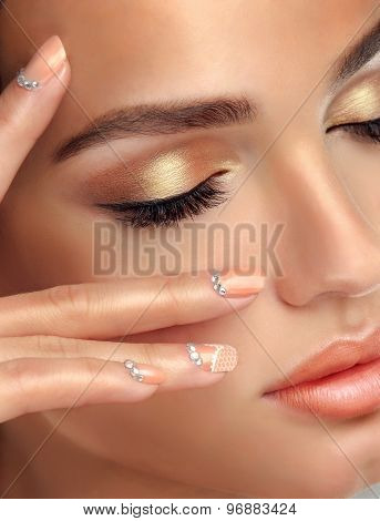 Makeup for eyes and lips ,eyeliner and coral lipstick. Beige trend manicured nails with rhinestones