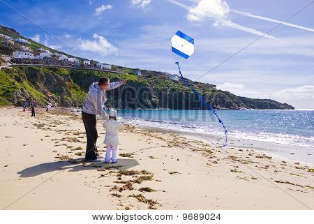 A Little Girl And Dad Run A Kite In The Sky With Clouds On The Beach Near The Sea...