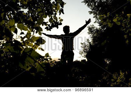 Silhouette Young Man Opening His Arms At The Field