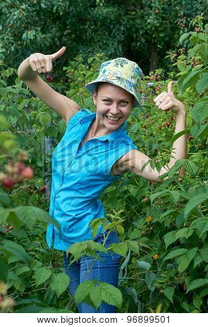 Cheerful, Young Girl In The Garden, Standing With Raspberries In The Mouth