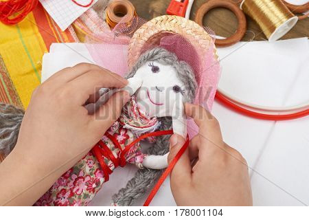 child hand making dress for handmade doll, learn to sewing