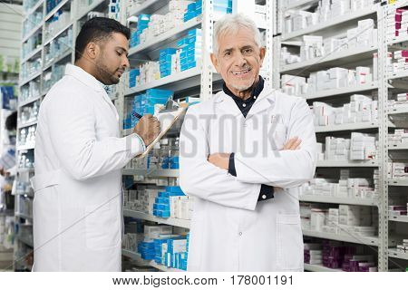 Senior Chemist Standing Arms Crossed While Colleague Counting St