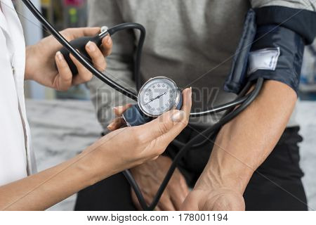Nurse Holding Gauge While Measuring Blood Pressure Of Patient