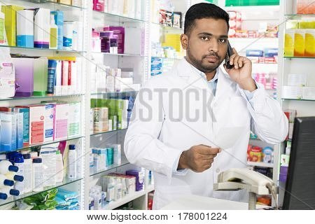Pharmacist Using Phone While Holding Prescription Paper