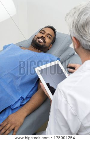 Radiologist Using Digital Tablet By Patient Lying On Bed