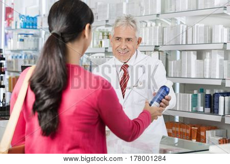 Pharmacist Selling Deodorant Bottle To Woman