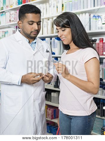 Woman Looking At Product Held By Chemist In Pharmacy