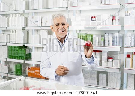 Pharmacist Showing Medicine Box At Counter