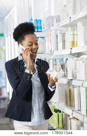 Woman Holding Medicine Box While Communicating On Mobile Phone