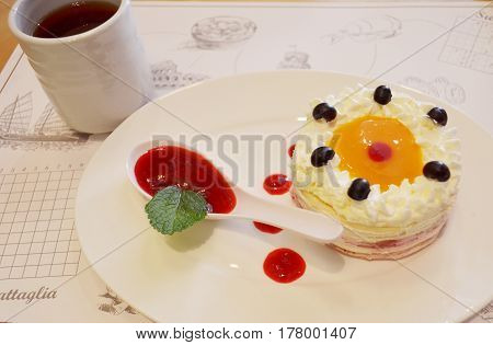 Cake With Cream And Blueberries And A Porcelain Spoon With Red Jam On A White Plate