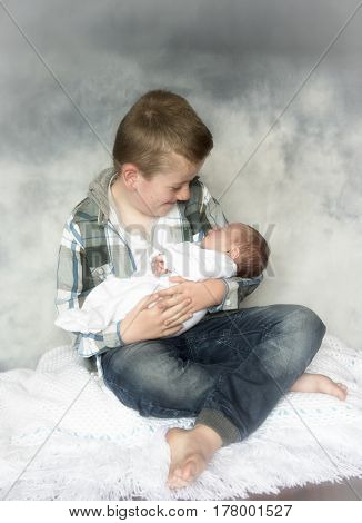 Family portrait image of a young boy holding a newborn baby.