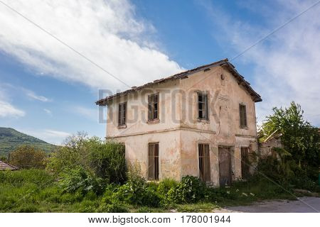 Old abandoned village house, blue cloudy sky