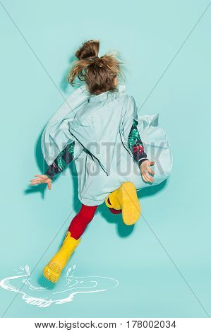 Little girl posing in fashion style wearing autumn clothing on blue background. Rubber yellow boots.