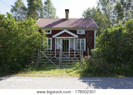 Cozy red summer house with wooden fence.