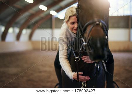 Blonde female sitting astride and hugging horse with eyes closed indoors riding hall.