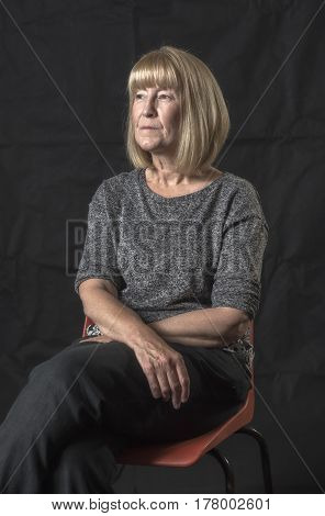 Close up portrait image of a mature blonde woman sitting down, Taken on a black background.