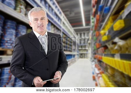 smiling adult businessman manager in a supermarket