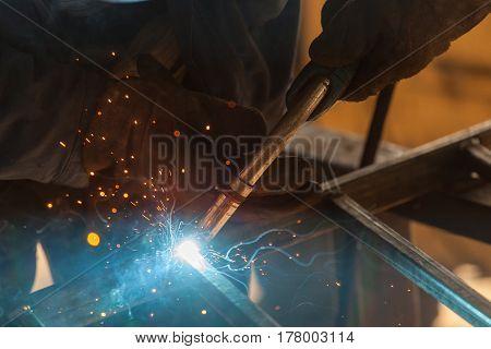 worker welding metal. Sparks from welding metal.