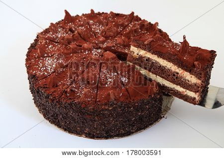 delicious chocolate cake with one piece cut from the whole cake