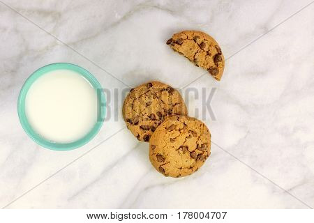 Chocolate chips cookies, shot from above on a white marble background, with a glass of milk and a place for text