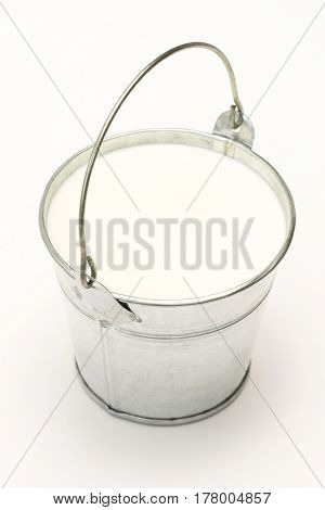 Metal pail Bucket full of milk on a white background