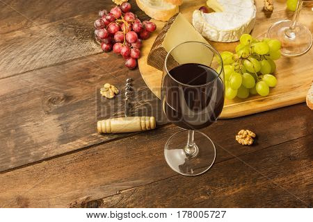 A photo of a wine and cheese tasting. Purple and green grapes, selection of cheeses, a glass of red wine, a place for text