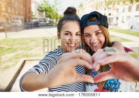 Two Romantic Girlfriends Making A Heart Gesture